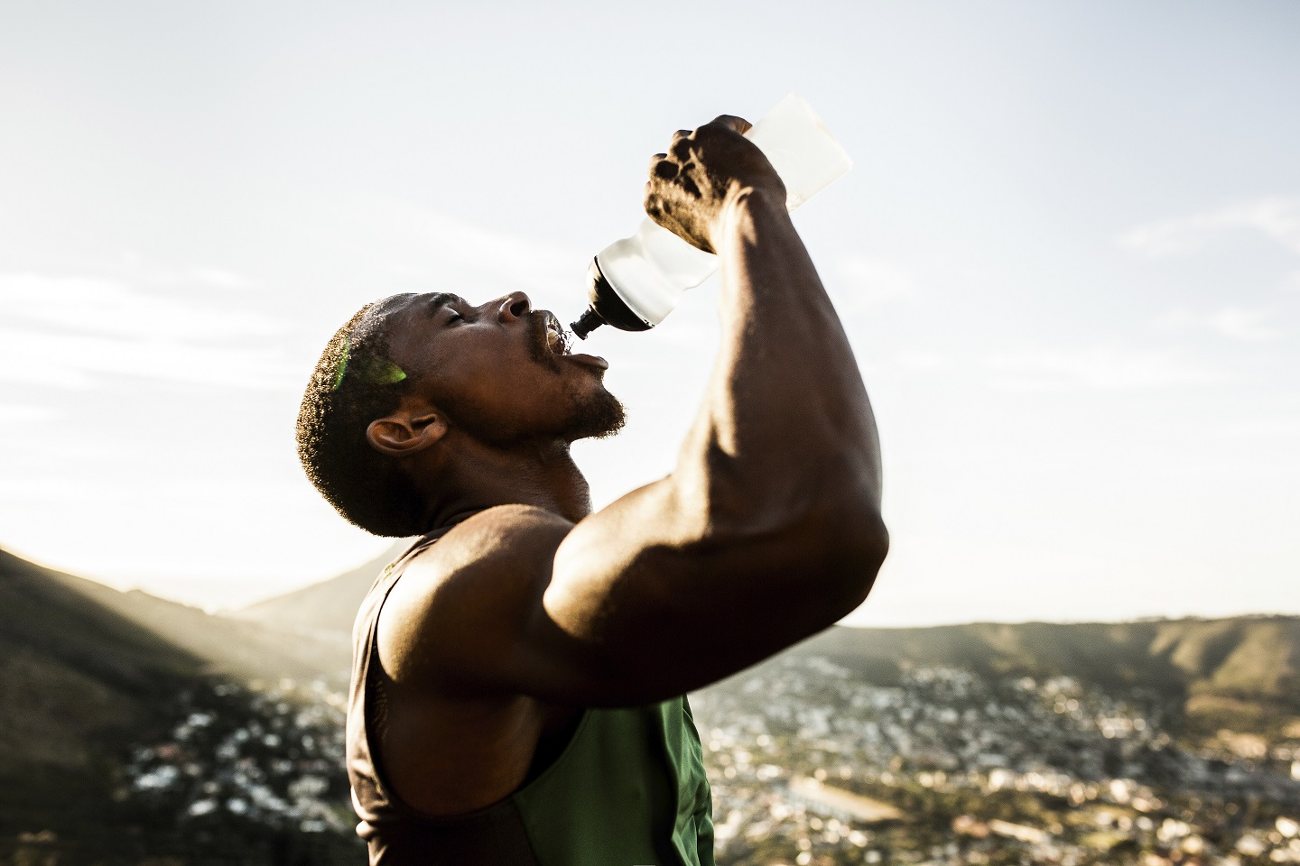Thirsty African American athlete pouring water into his mouth after a morning run