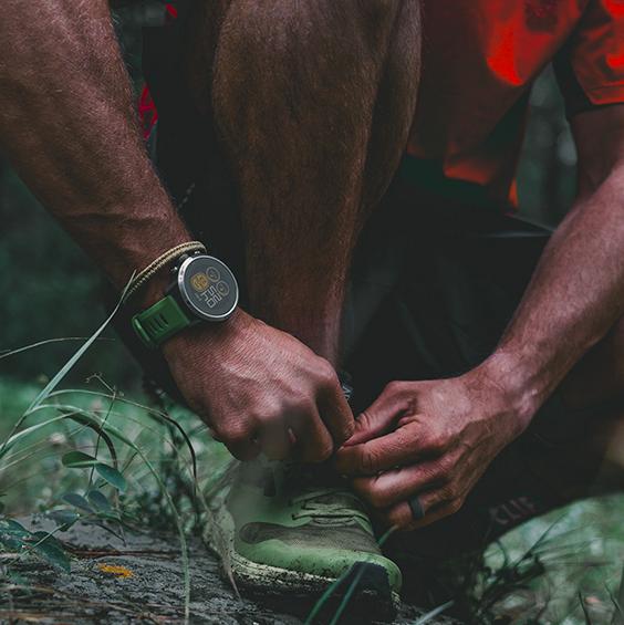 Homme qui fait ses lacets et qui porte sur son bras une montre coros apex pro avec un bracelet vert.
