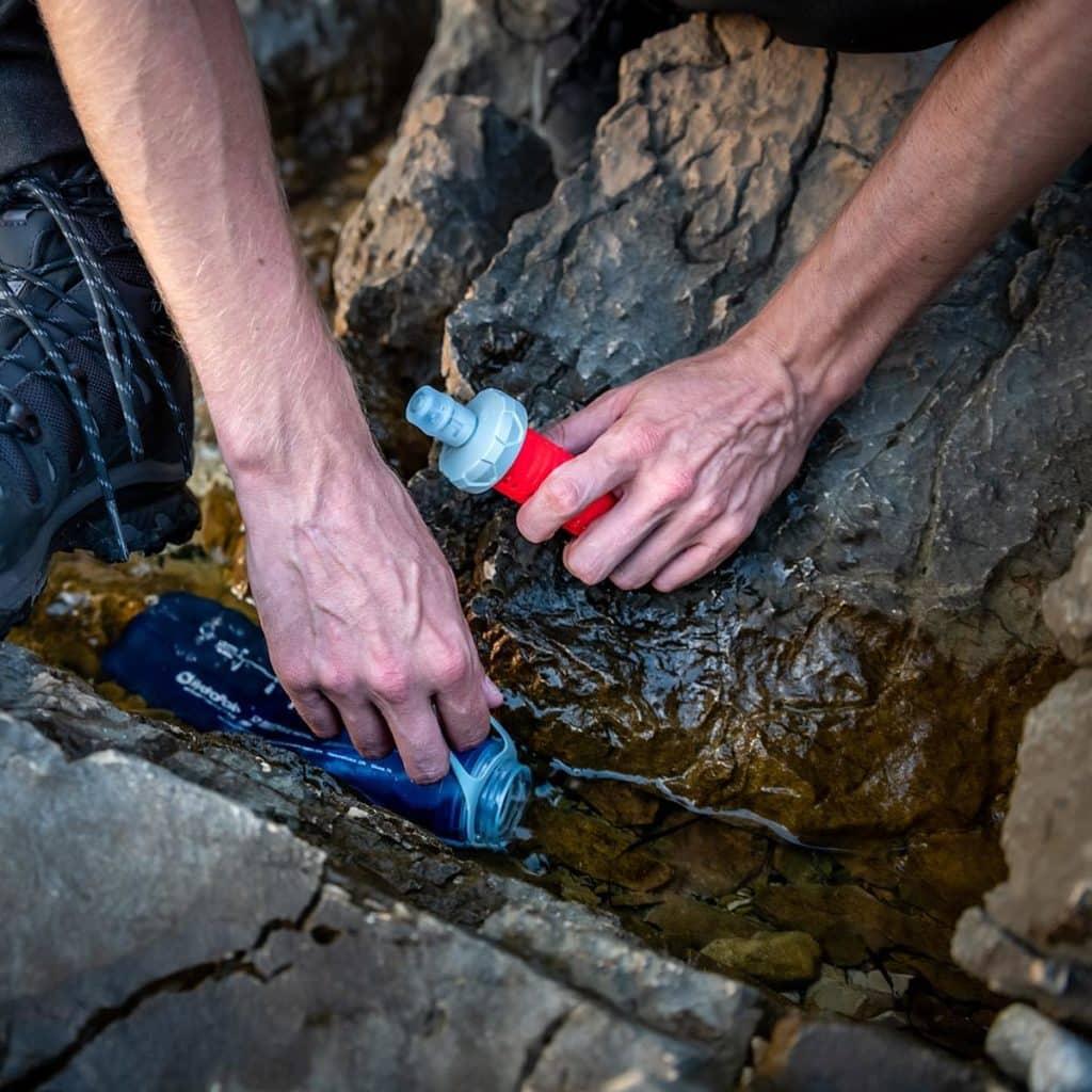 Personne qui tremple sa flasque d'eau dans un ruisseau.